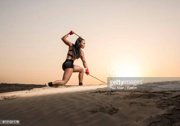 young woman jumping on sand against sky - aikāne stock pictures, royalty-free photos & images