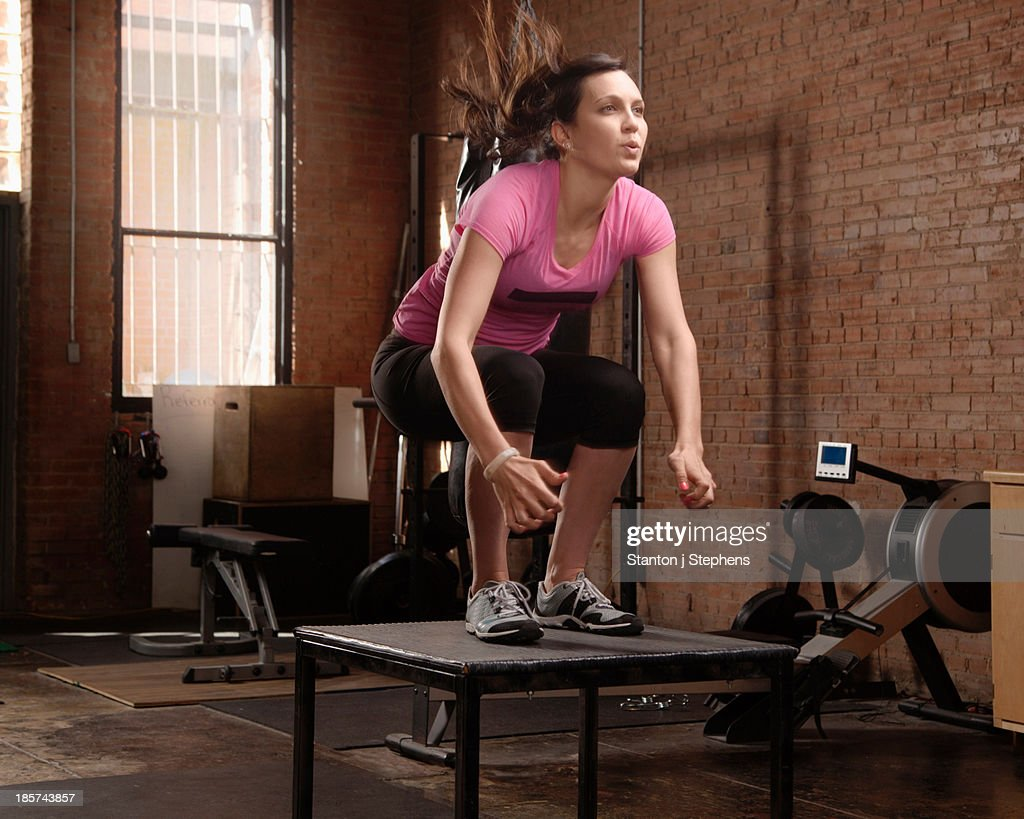 Young woman jumping on table in gym : Stock Photo