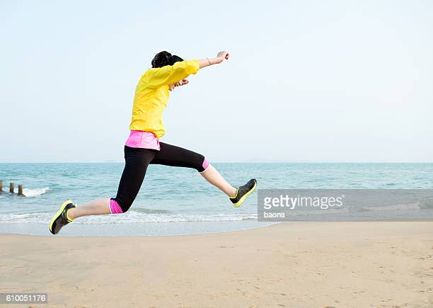 young woman jumping on the beach - skipping along stock pictures, royalty-free photos & images