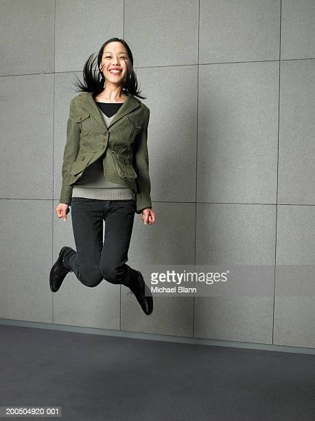 Young woman jumping on the spot, smiling, portrait