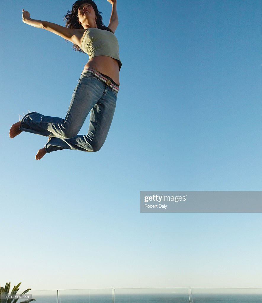 Young Woman Jumping On Trampoline Arms Outstretched Low -4385