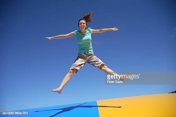 Young woman jumping on trampoline, smiling