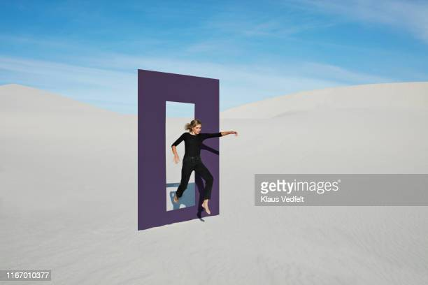 young woman jumping on white sand through door frame at desert - porta foto e immagini stock