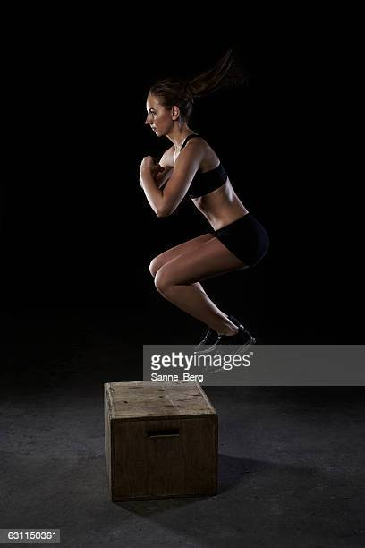 Young woman jumping on wooden box in gym