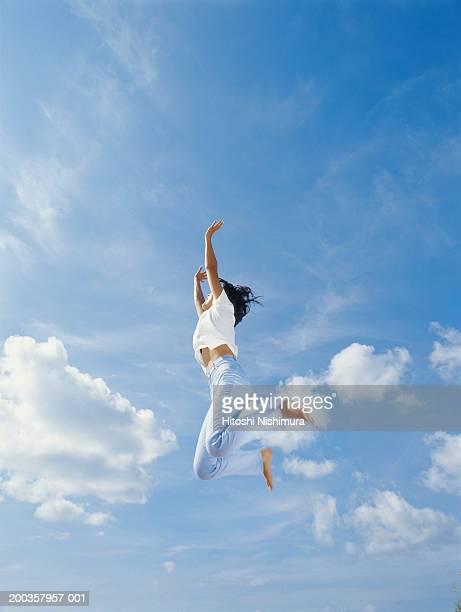 Young woman jumping outdoors, low angle view