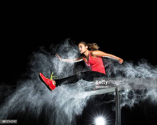 Young woman jumping over hurdle in between cloud of flour