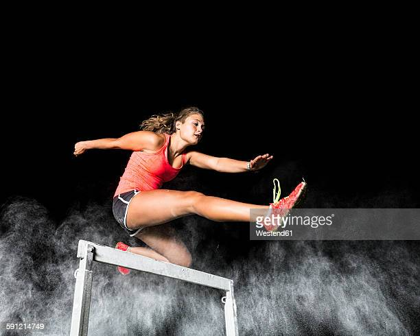 Young woman jumping over hurdle