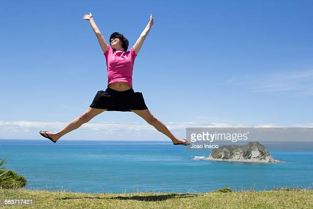 Young woman jumping over idyllic landscape