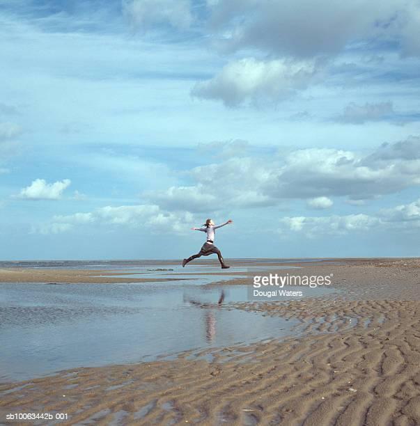 Young woman jumping over water on beach, side view
