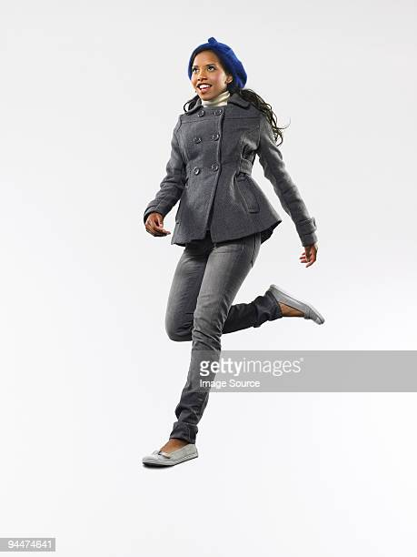 young woman jumping - black coat stock pictures, royalty-free photos & images