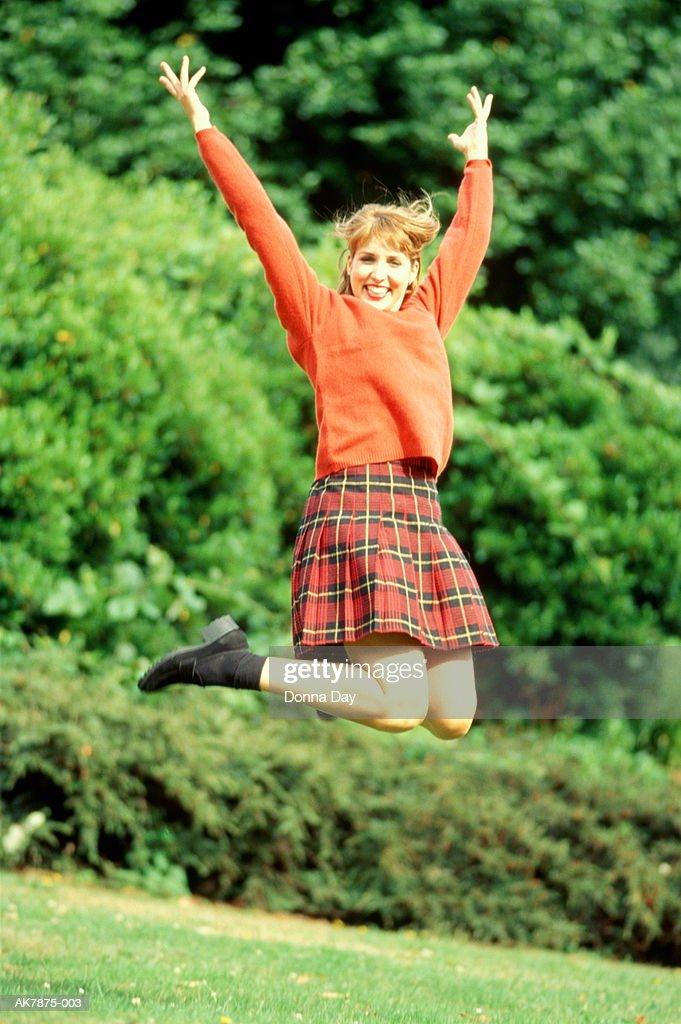 Young woman jumping, raising arms above head, portrait, outdoors : Stock Photo