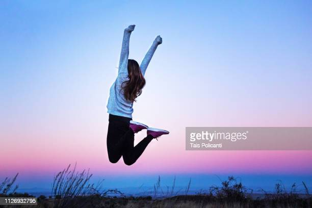 young woman jumping raising her arms at a colorful sunset - aragon, spain - aspiration photos et images de collection