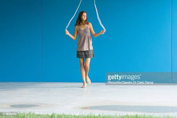 young woman jumping rope, front view, full length - ado minijupe photos et images de collection
