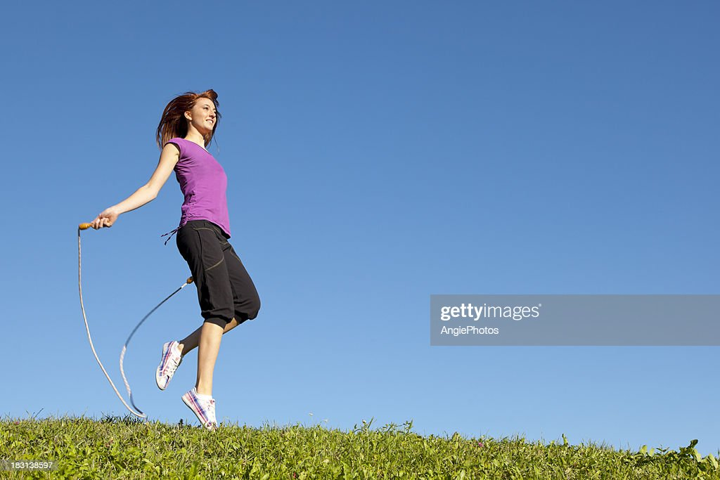 Young woman jumping rope : Stock Photo