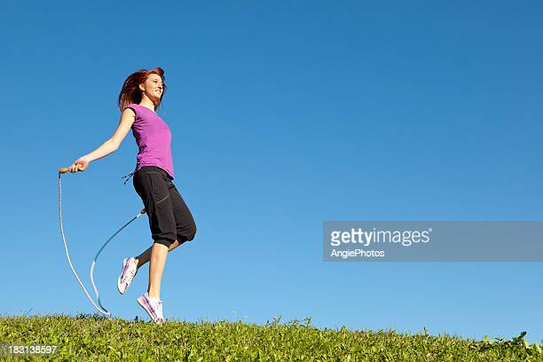 young woman jumping rope - skipping along stock pictures, royalty-free photos & images