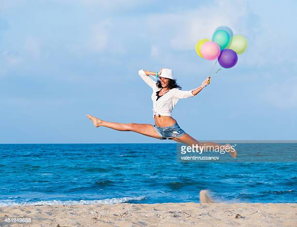 Young woman jumping with  balloons