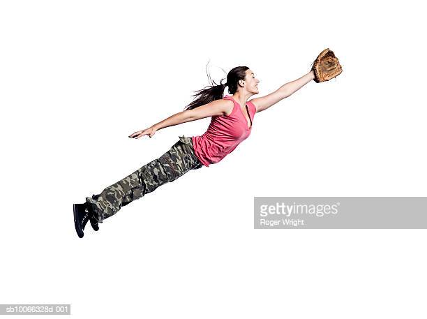 young woman jumping with baseball glove - diving to the ground stock pictures, royalty-free photos & images