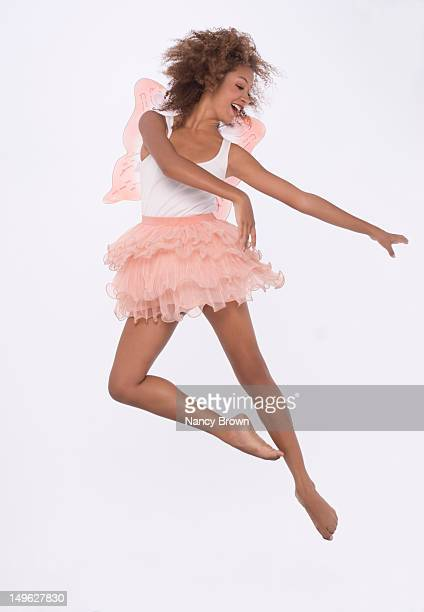 Young woman jumping with fairy wings