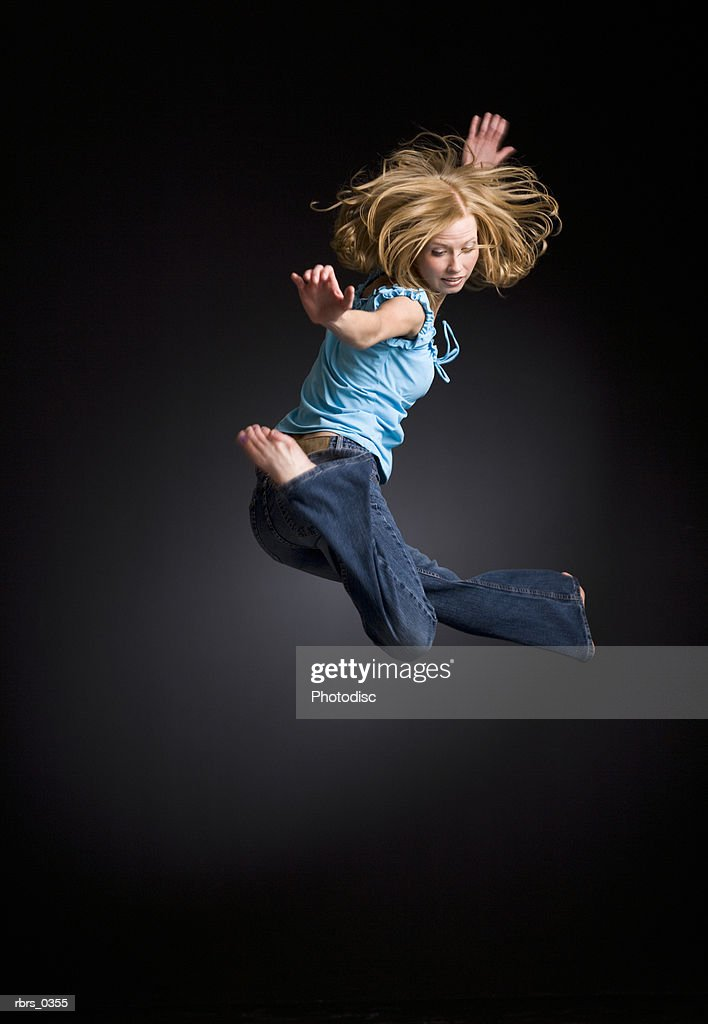 Young woman jumping with her arms outstretched : Foto de stock