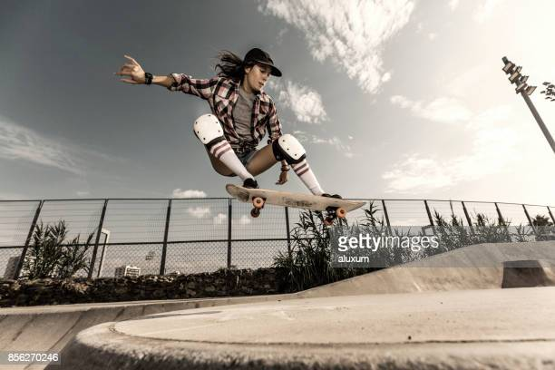 Young woman jumping with skateboard