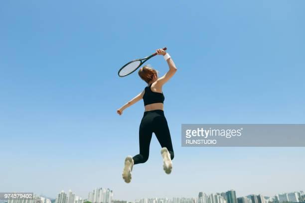 young woman jumping with tennis racket - atlete stockfoto's en -beelden