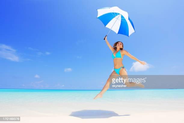 Mujer joven saltar con sombrilla en la Playa exótica.