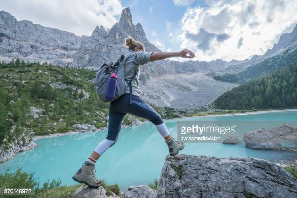 Young woman jumps rock to rock near mountain lake, Dolomites, Italy