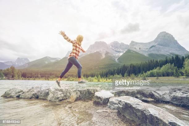 若い女性は山の湖で岩をジャンプします。