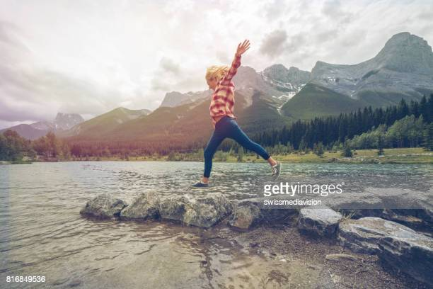 Young woman jumps rock to rock on mountain lake