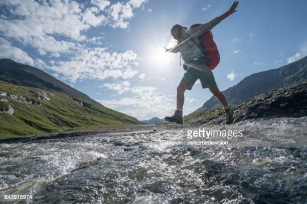 Jeune femme saute de rocher en rocher sur la rivière de montagne