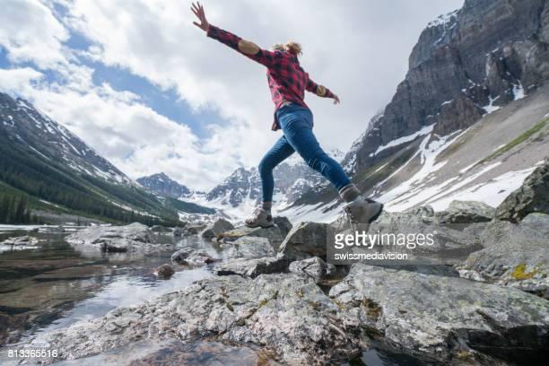 Junge Frau springt auf Felsen am Bergsee