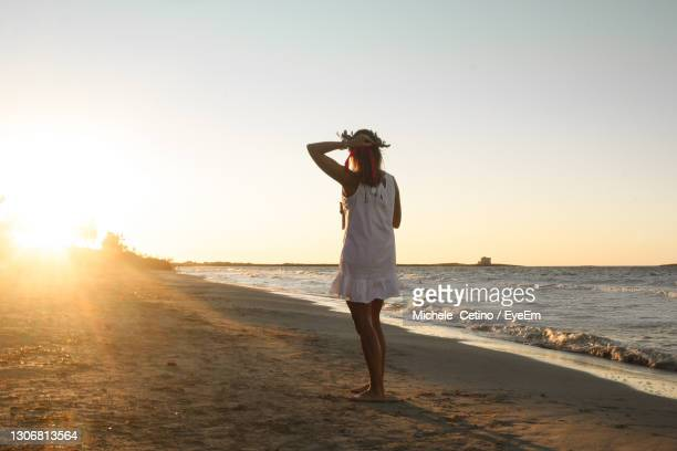 young woman just graduated walking on the beach at sunset with laurel wreath - ブリンディシ ストックフォトと画像