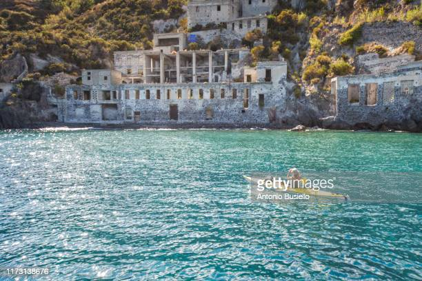 young woman kayaking in front of a pumice quarry in lipari - insel lipari stock-fotos und bilder