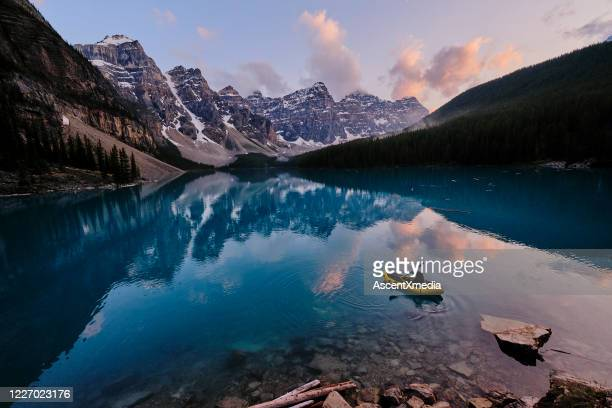 young woman kayaks across mountain lake at sunrise - canada stock pictures, royalty-free photos & images