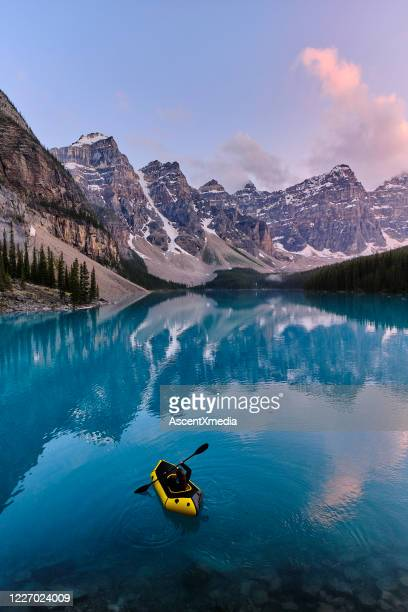 young woman kayaks across mountain lake at sunrise - canadian rockies stock pictures, royalty-free photos & images