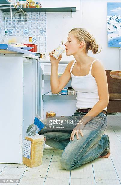 Young woman keeing in front of refrigerator in kitchen