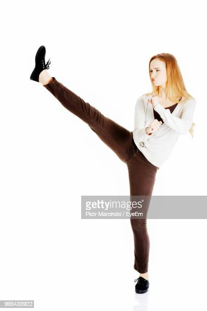young woman kicking against white background - kicking ストックフォトと画像