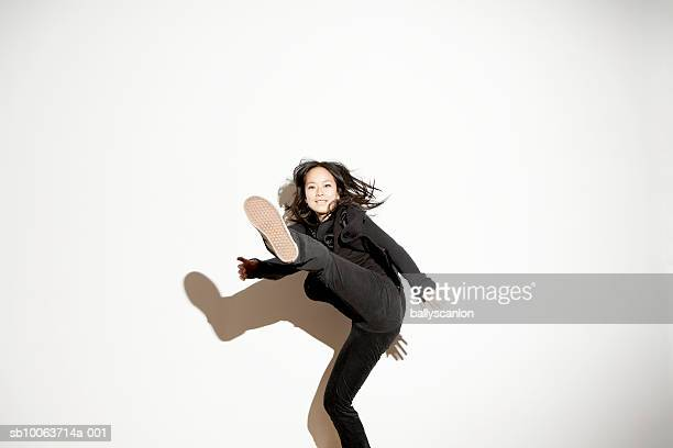 young woman kicking in mid-air - kicking stock pictures, royalty-free photos & images
