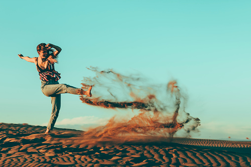 Young woman kicking sand in desert landscape - gettyimageskorea
