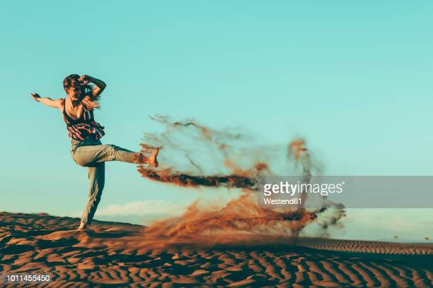 young woman kicking sand in desert landscape - zorgeloos stockfoto's en -beelden