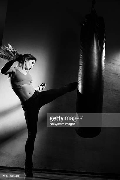 Junge Frau treten die Tasche im Fitnessstudio