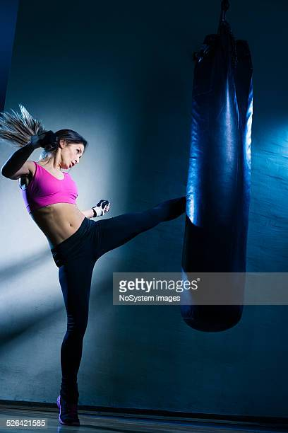 Young woman kicking the bag at the gym