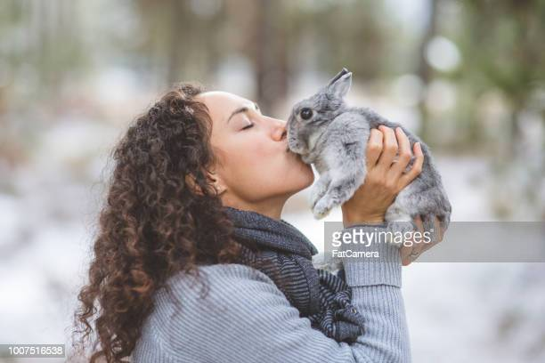 Young woman kisses her rabbit on a hike out in the snow