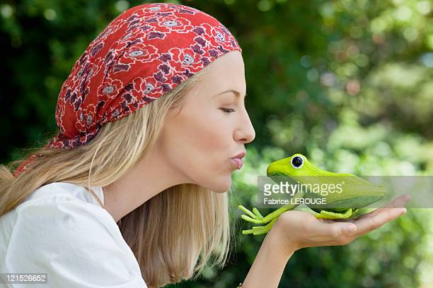 Young woman kissing a frog toy