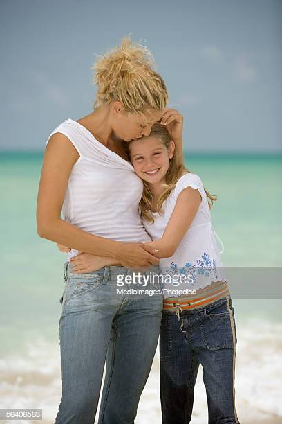 Young woman kissing a girl on the beach