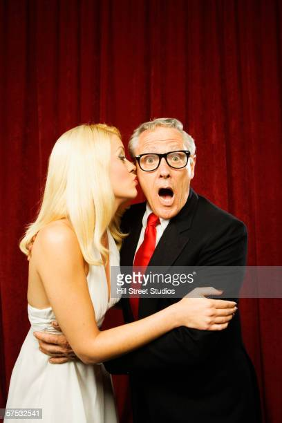 young woman kissing a shocked older man - old man young woman stock photos and pictures
