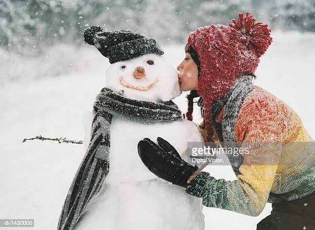 Young Woman Kissing a Snowman