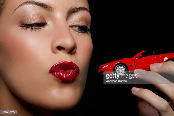 Young woman kissing a toy car, portrait.