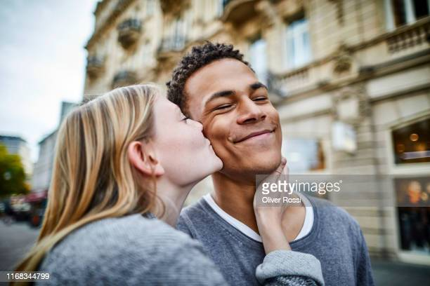 young woman kissing boyfriend in the city - heterosexuelles paar stock-fotos und bilder
