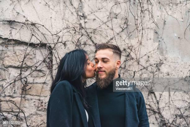 Young woman kissing boyfriend on his cheek